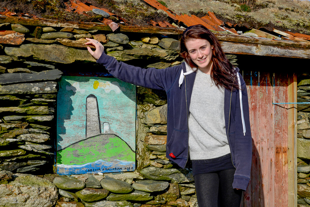 Carina O'Halloran (19years old) with the painting she painted as an 8 year old durinf an Art Project run by artist Lol Hardman from Clifden. The artworks all painted by children from the island were installed into ruined buildings to brighten up the villages. Inishbofin, Co Galway, Ireland.
