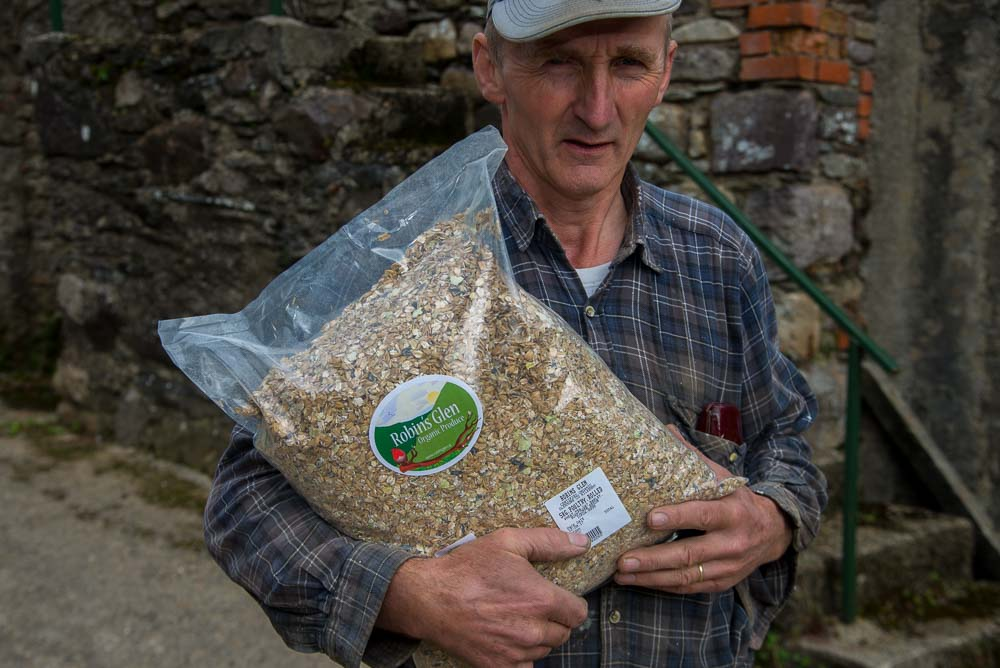 Richard Murphy, Glen Organic Farm, Glenmore, County Kilkenny, Ireland, with rolled Corn animal feed.
